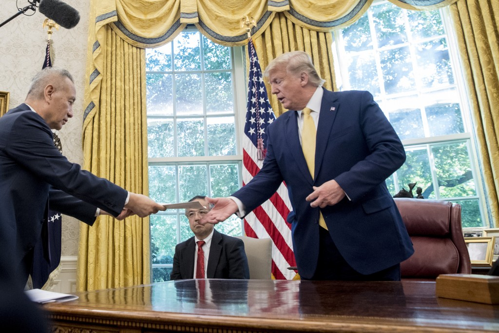 President Donald Trump receives a letter presented to him by Chinese Vice Premier Liu He, left, in the Oval Office of the White House in Washington, F...