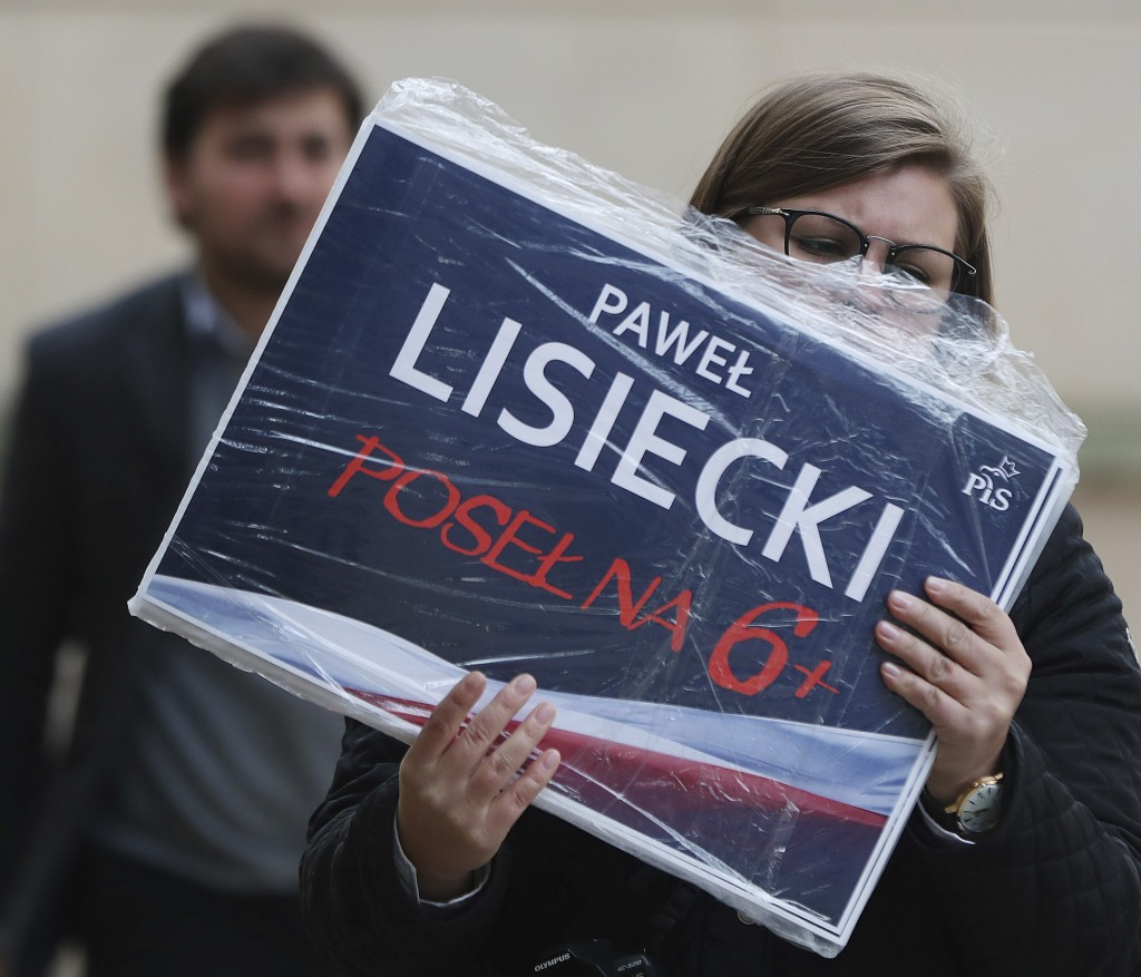 In this photo taken Tuesday Oct. 8, 2019 a supporter of Poland's ruling right-wing party is holding photos of one of the Law and Justice party's candi