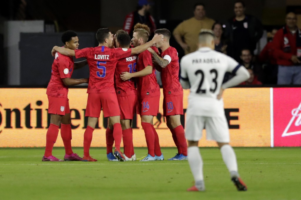 U.S players celebrate a goal by Weston McKennie, left, as Cuba's Luis Paradela (23) stands nearby during the first half of a CONCACAF Nations League s
