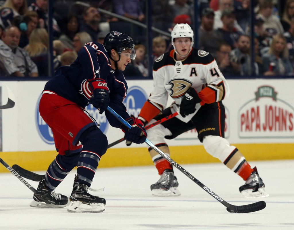 Columbus Blue Jackets forward Sonny Milano, left, controls the puck in front of Anaheim Ducks defenseman Josh Manson during the first period of an NHL