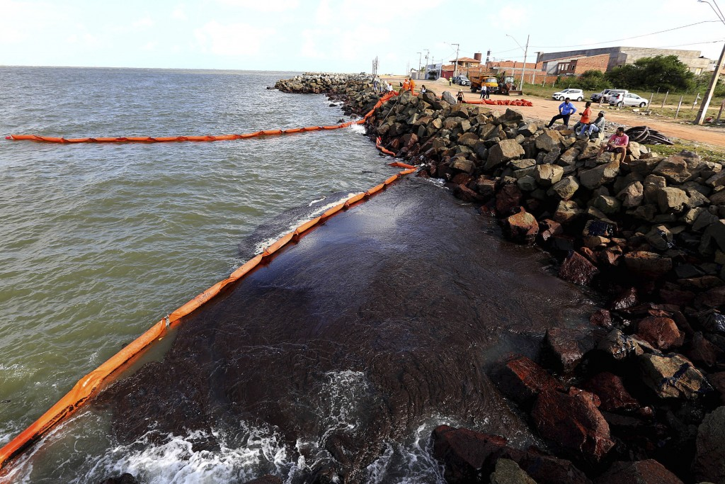 This Oct. 4, 2019 handout photo released by the Aracaju Municipal Press Office, shows rocks stained by an oil spill, on Artistas Beach, in Aracaju, Br