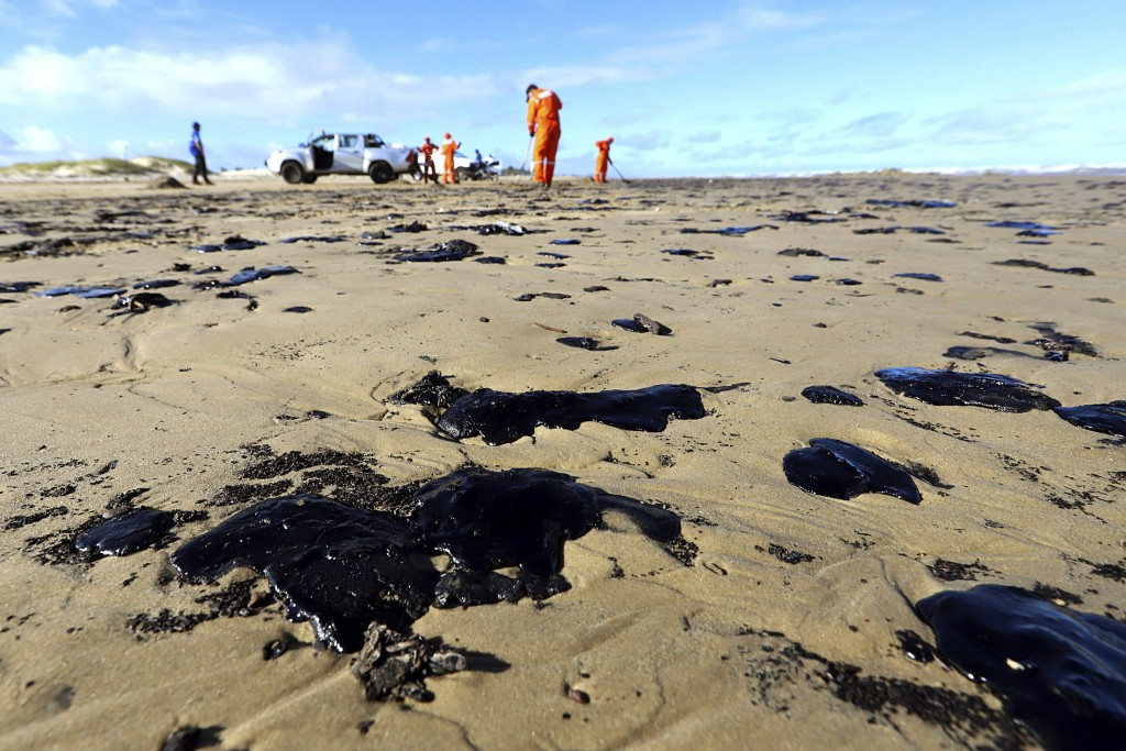 CORRECTS DATE - In this Oct. 7, 2019 handout photo released by the Aracaju Municipal Press Office, workers remove oil from Viral Beach, in Aracaju, Br