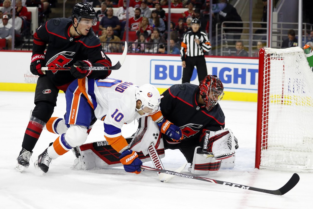 Carolina Hurricanes goaltender Petr Mrazek (34), of the Czech Republic, gloves the puck in front of a charging New York Islanders' Derick Brassard (10...