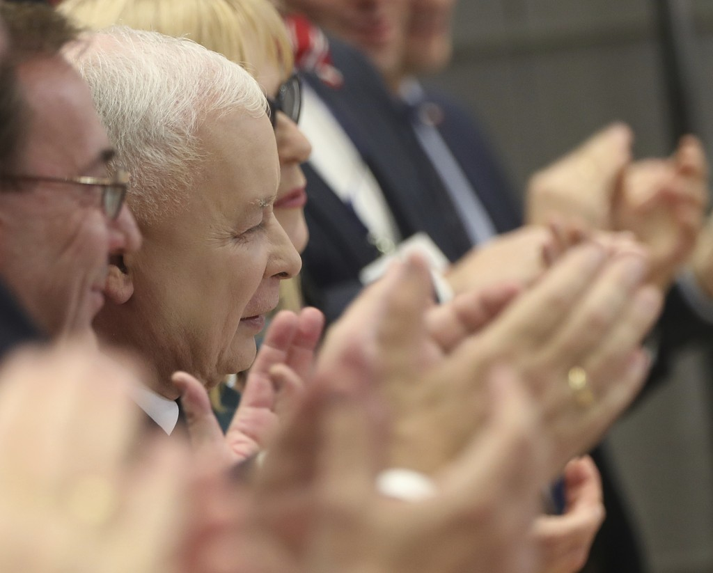 In this photo taken Tuesday Oct. 8, 2019 Poland's ruling right-wing party leader Jaroslaw Kaczynski,center, is applauded by party members after he spo...