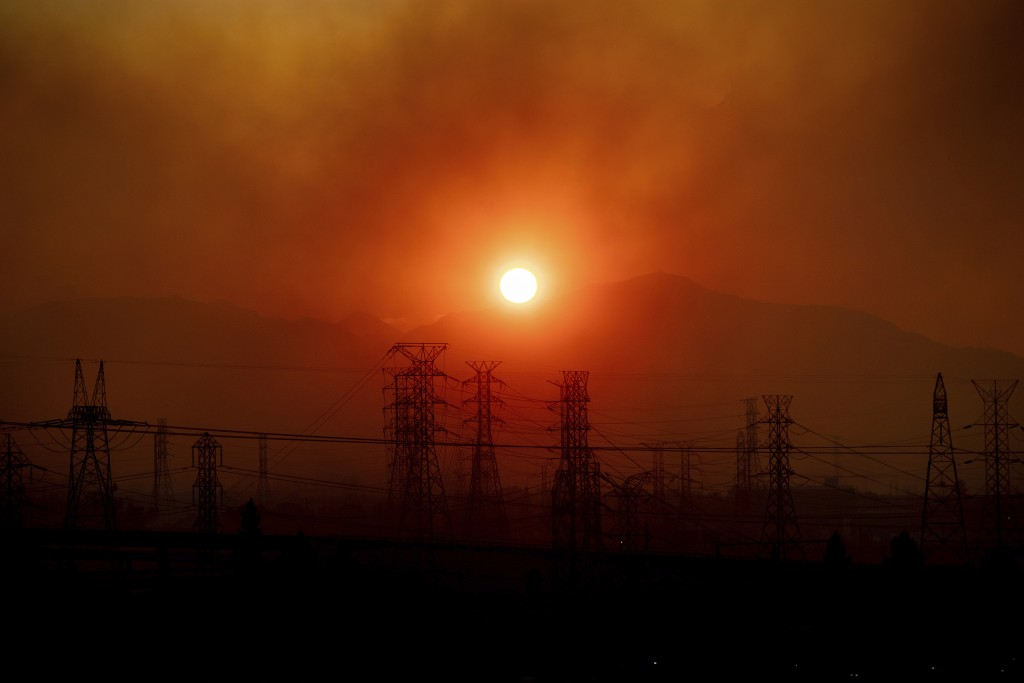 Smoke from the Saddleridge Fire hangs above power lines as the sun rises in Newhall, Calif., on Friday, Oct. 11, 2019. An aggressive wildfire in South...