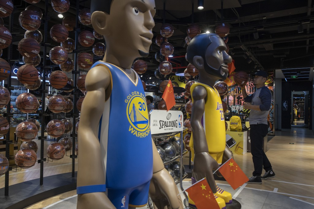 In this Friday, Oct. 11, 2019, photo, a shopper reach holds a basketball near statues of NBA players Stephen Curry of the Golden State Warriors, left,