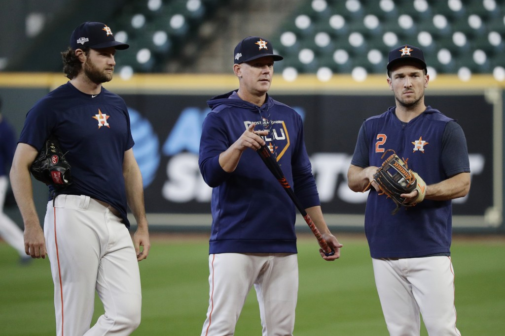 Houston Astros starting pitcher Gerrit Cole, left, manager AJ Hinch, center, and third baseman Alex Bregman, right, talk during a practice for a baseb