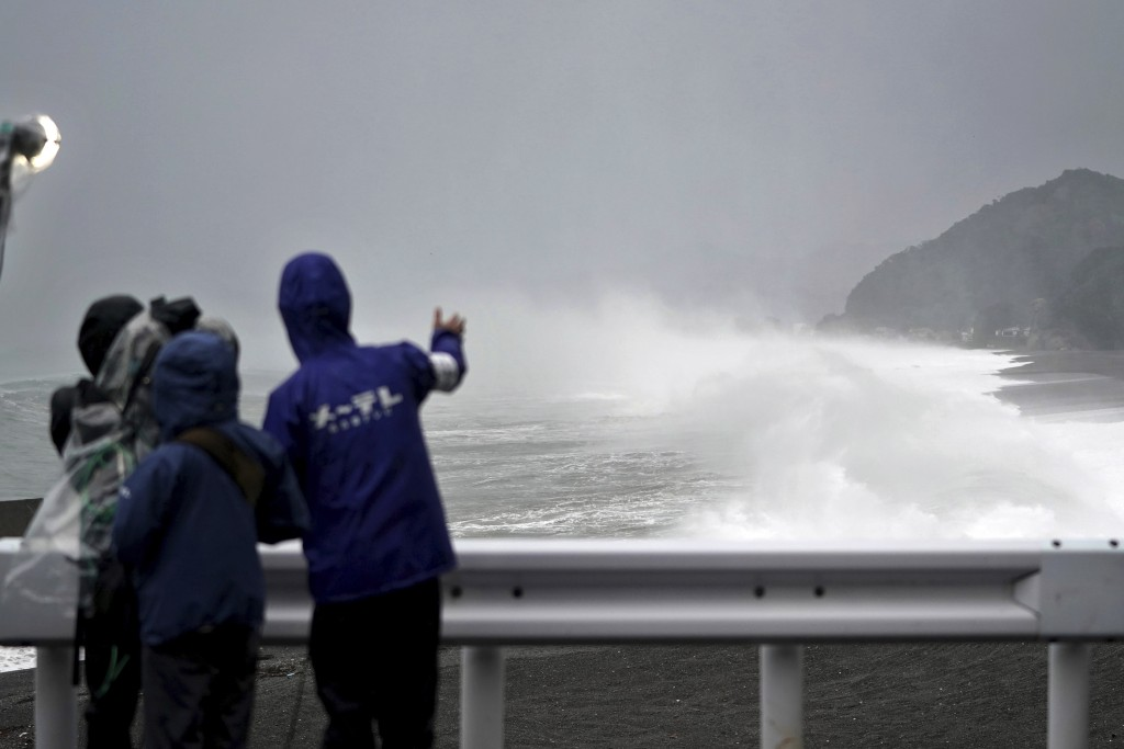 A local television crew reports on the surging waves as Typhoon Hagibis approaches a beach in Kumano, Mie Prefecture, Japan, Saturday, Oct. 12, 2019. ...