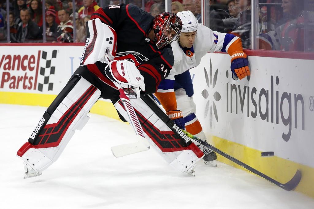 Carolina Hurricanes goaltender Petr Mrazek (34) of the Czech Republic, clears the puck away from New York Islanders' Matt Martin (17) during the first