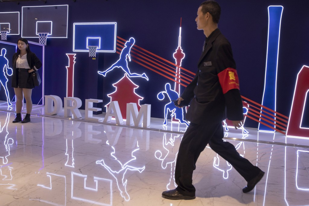 In this Friday, Oct. 11, 2019, photo, a security guard walks past neon light decor depicting basketball players and silhouette of iconic Chinese build
