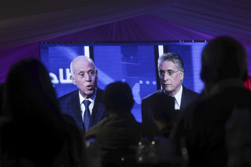 CORRECTS POSITION - People watch a televised debate between presidential candidates Kais Saied, left, and Nabil Karoui, on the last day of campaigning