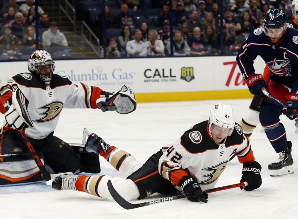 Anaheim Ducks defenseman Josh Manson, center, tries to control the puck in front of Ducks goalie Ryan Miller, left, and Columbus Blue Jackets forward