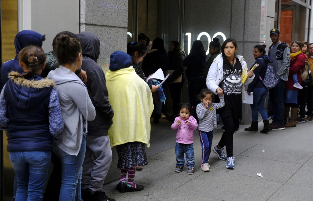 File - In this Jan. 31, 2019, file photo, hundreds of people overflow onto the sidewalk in a line snaking around the block outside a U.S. immigration ...