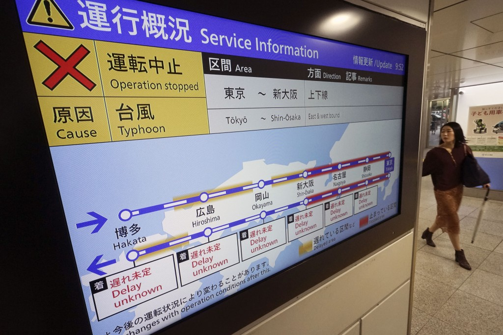 A passenger walks past an update notice on suspending operations of the Shinkansen or bullet train on Oct. 12-13 due to Typhoon Hagibis, at Tokyo Stat