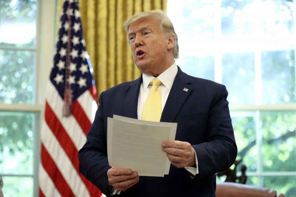 President Donald Trump holds a letter as he meets with Chinese Vice Premier Liu He in the Oval Office of the White House in Washington, Friday, Oct. 1...