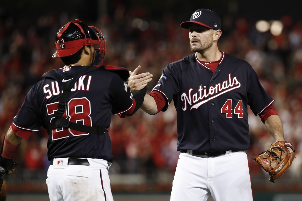 Washington Nationals relief pitcher Daniel Hudson (44) and catcher Kurt Suzuki (28) celebrate the final of Game 4 of a baseball National League Divisi...