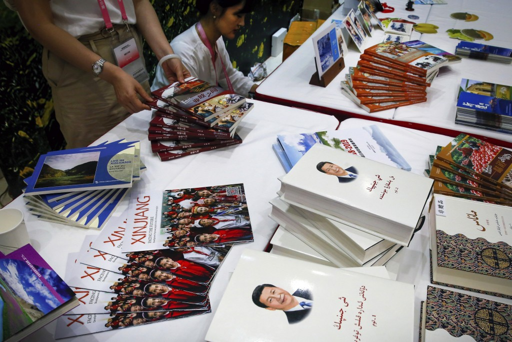 FILE - In this July 30, 2019, file photo, copies of the book on the governance of Chinese President Xi Jinping are displayed with booklets promoting X