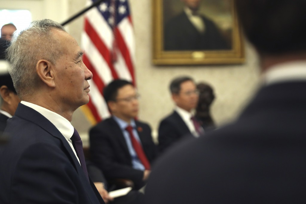 Chinese Vice Premier Liu He listens during a meeting with President Donald Trump in the Oval Office of the White House in Washington, Friday, Oct. 11,...