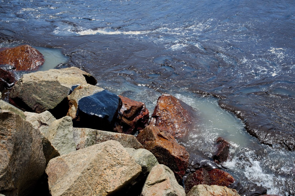 In this Sept. 25, 2019 photo released by the Sergipe state Government, oil sludge floats near the rocks at the Coroa do Meio beach, in Sergipe state,