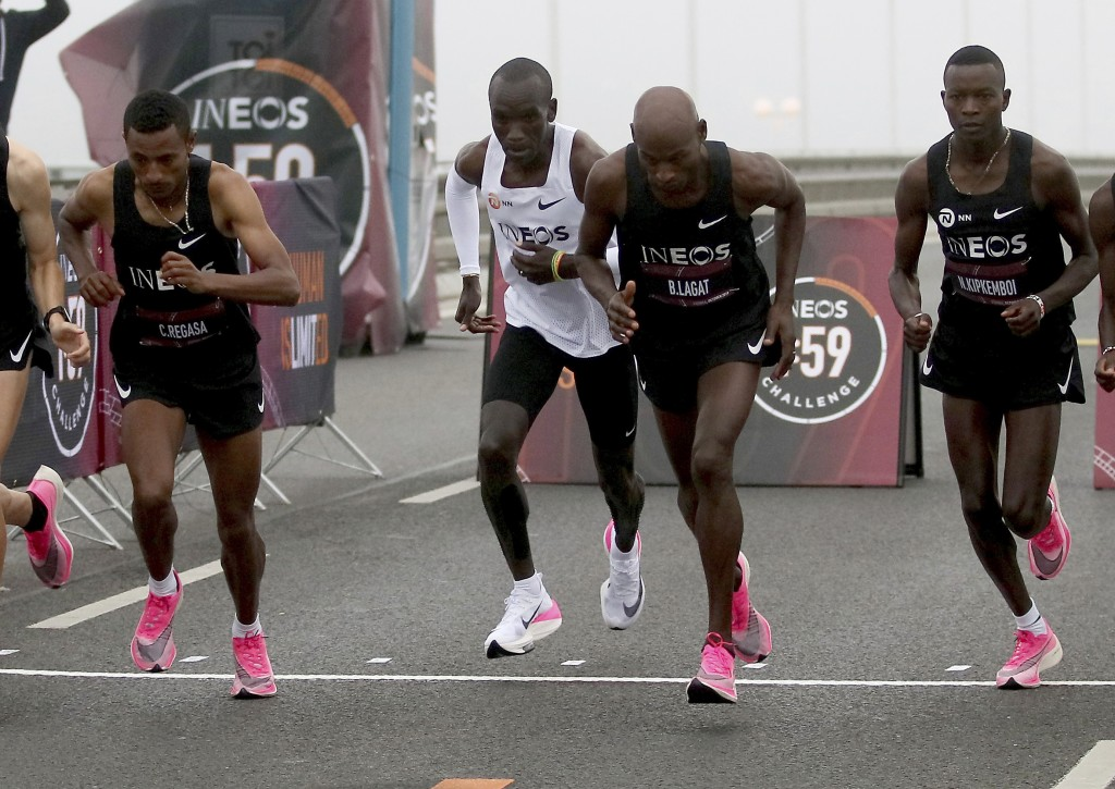 Marathon runner Eliud Kipchoge from Kenya, white vest, and his first pacemaking team leave the start line on Reichsbrucke during the INEOS 1:59 Challe...