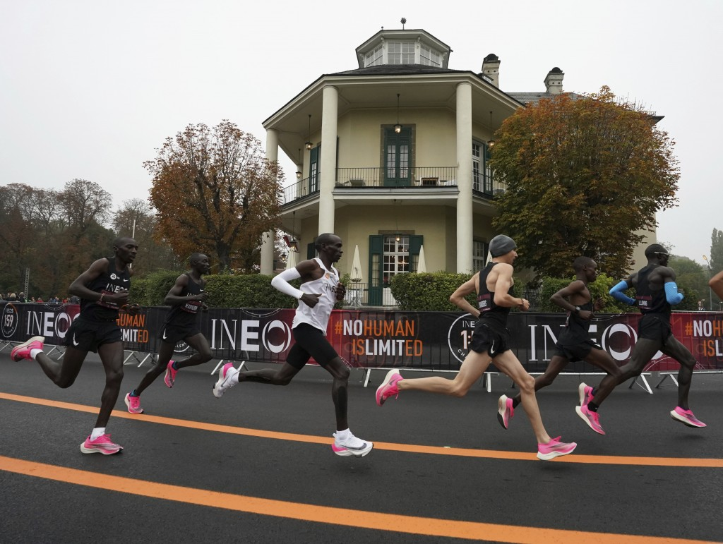 In this photo made available by The INEOS 1:59 Challenge on Saturday, Oct. 12, 2019, Eliud Kipchoge, white vest, runs past the Lusthaus with his pacem...