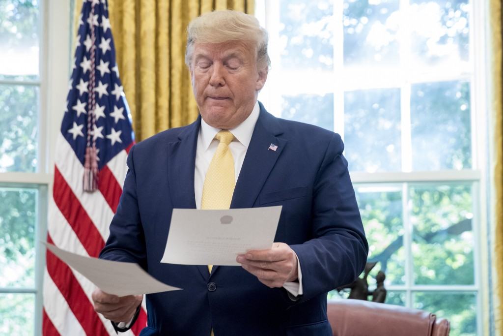 President Donald Trump holds a letter presented to him by Chinese Vice Premier Liu He, left, in the Oval Office of the White House in Washington, Frid...
