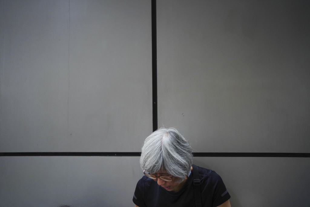 A protester takes part in a sit in outside police headquarters during a protest in Hong Kong, Saturday, Oct. 12, 2019. The protests that started in Ju