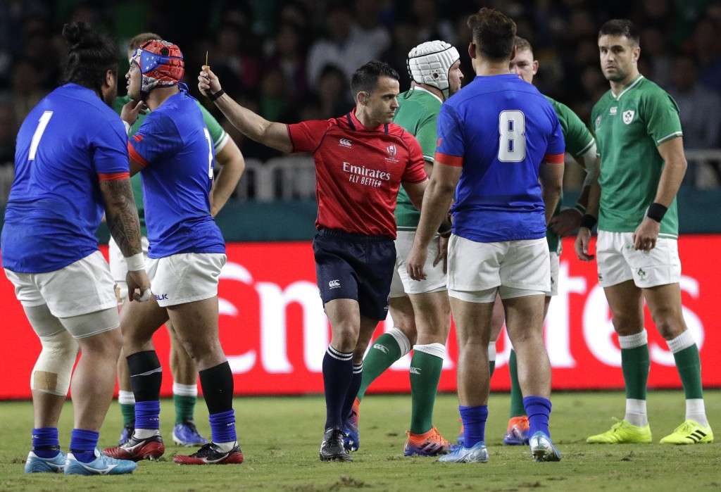 Referee Nic Berry shows a yellow card to Samoa's Seilala Lam, second left, during the Rugby World Cup Pool A game at Fukuoka Hakatanomori Stadium betw...