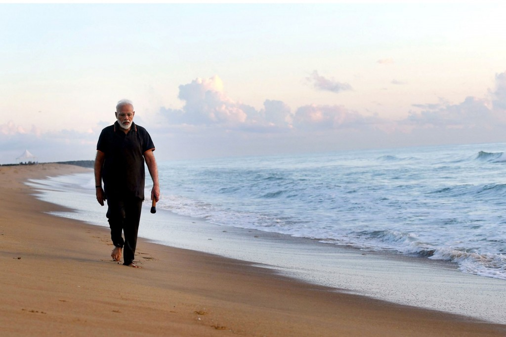 In this photo provided by Prime Minister of India Narendra Modi's twitter handle, Indian Prime Minister Narendra Modi takes morning walk at a beach in...