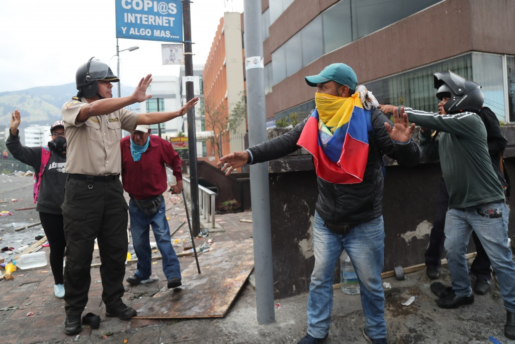 Anti-government protesters abandon their position near the National Assembly after security forces launched tear gas to disperse them, in Quito, Ecuad...