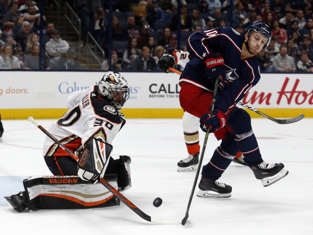 Anaheim Ducks goalie Ryan Miller, left, stops a shot behind Columbus Blue Jackets forward Alexander Wennberg, of Sweden, during the second period of a