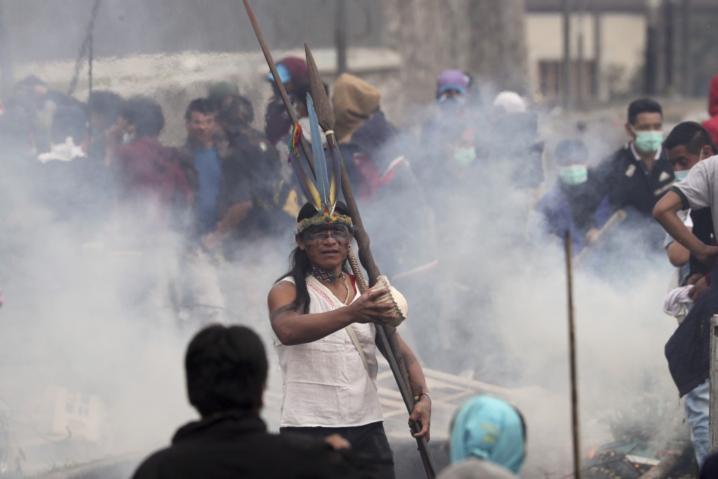 Anti-government demonstrator stands in the middle of tear gas during clashes with police in Quito, Ecuador, Friday, Oct. 11, 2019. Protests, which beg
