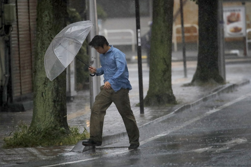 A man crosses the road in Hamamatsu, central Japan, Saturday, Oct. 12, 2019. A heavy downpour and strong winds pounded Tokyo and surrounding areas on