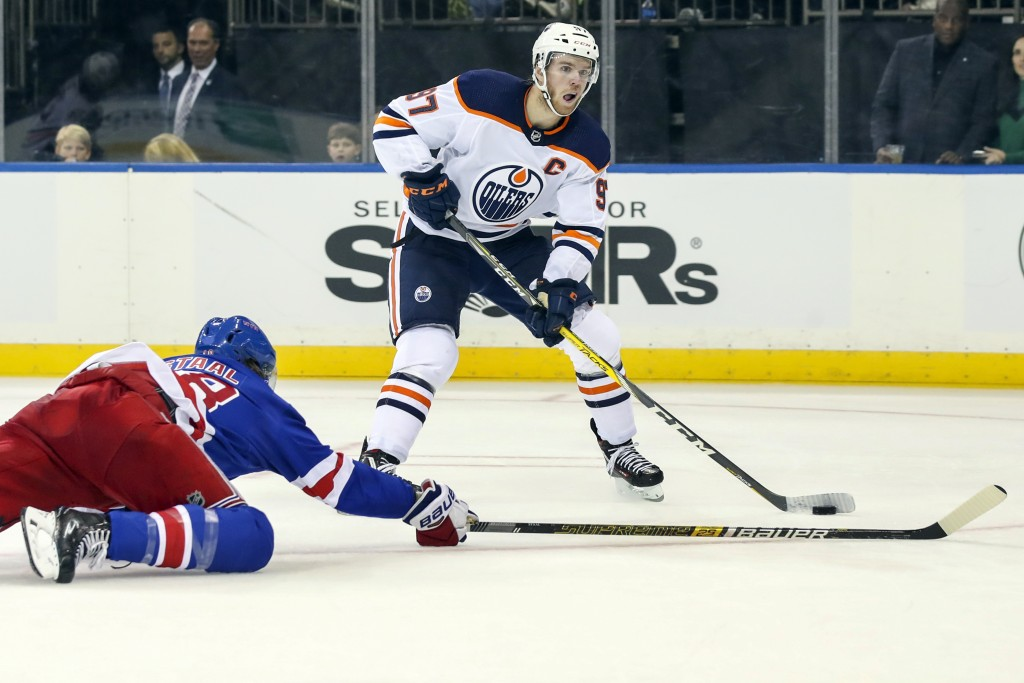 Edmonton Oilers center Connor McDavid (97) skates against New York Rangers defenseman Marc Staal (18) during the third period of an NHL hockey game, S...