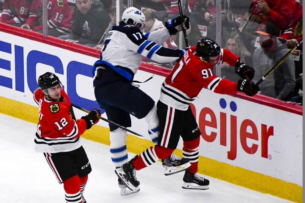 Winnipeg Jets left wing Adam Lowry (17). Checks Chicago Blackhawks center Drake Caggiula (91) as right wing Alex DeBrincat (12) looks on during the se...