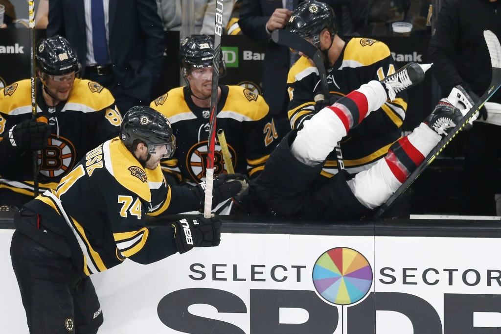 Boston Bruins' Jake DeBrusk (74) checks New Jersey Devils' Kevin Rooney into the Bruins' bench during the third period of an NHL hockey game in Boston