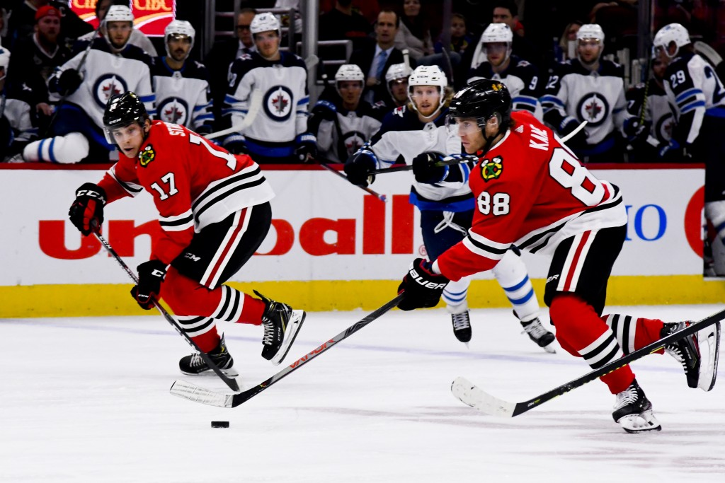 Chicago Blackhawks right wing Patrick Kane (88) and center Dylan Strome (17) move the puck during the first period of an NHL hockey game against the W...