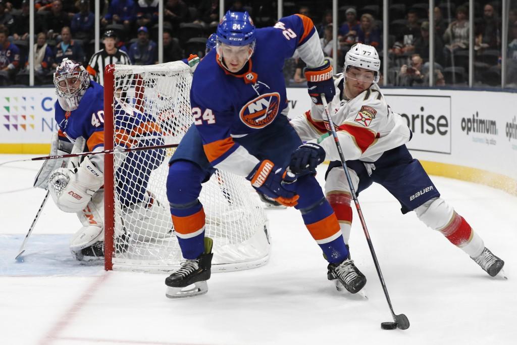 Florida Panthers center Frank Vatrano (77) tries to get the puck from New York Islanders defenseman Scott Mayfield (24) as Islanders goaltender Semyon...
