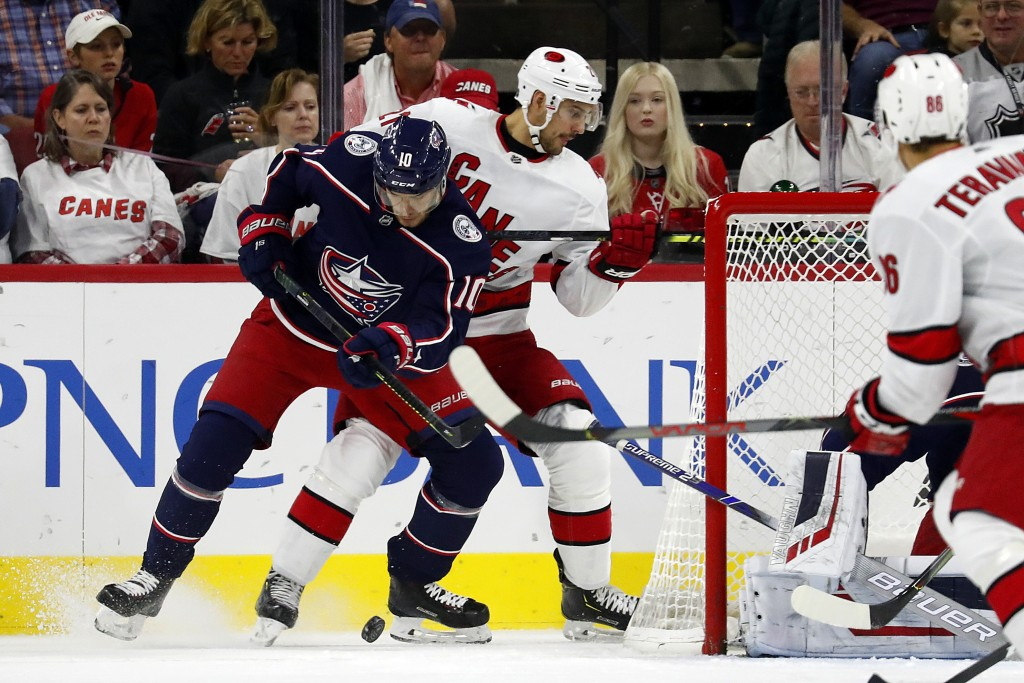 Columbus Blue Jackets' Alexander Wennberg (10), of Sweden, battles with Carolina Hurricanes' Nino Niederreiter (21), of the Czech Republic, for the pu...