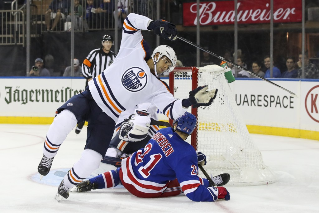 Edmonton Oilers defenseman Darnell Nurse trips over New York Rangers center Brett Howden (21) during the second period of an NHL hockey game, Saturday...
