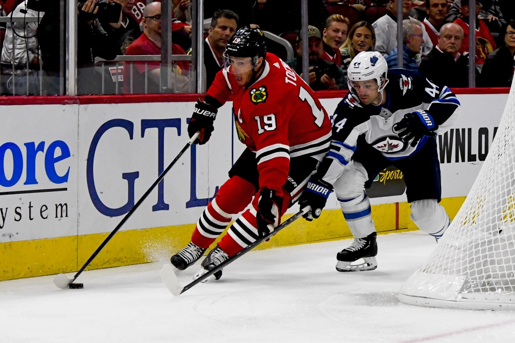 Chicago Blackhawks center Jonathan Toews (19) and Winnipeg Jets defenseman Josh Morrissey (44) fight for the puck during the first period of an NHL ho...