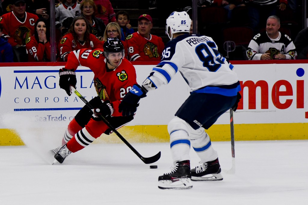 Chicago Blackhawks left wing Brandon Saad (20) moves the puck past Winnipeg Jets center Mathieu Perreault (85) During the first period of an NHL hocke...
