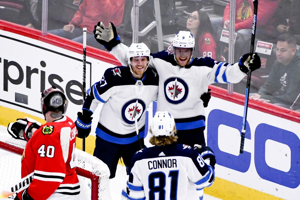 Winnipeg Jets center Andrew Copp (9) celebrates his goal against the Chicago Blackhawks with left wing Nikolaj Ehlers (27) and left wing Kyle Connor (