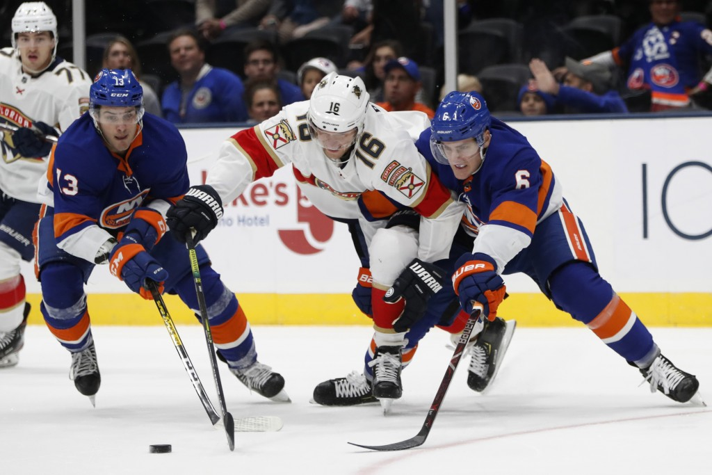 New York Islanders center Mathew Barzal (13) and defenseman Ryan Pulock (6) defend against Florida Panthers center Aleksander Barkov (16) during the f