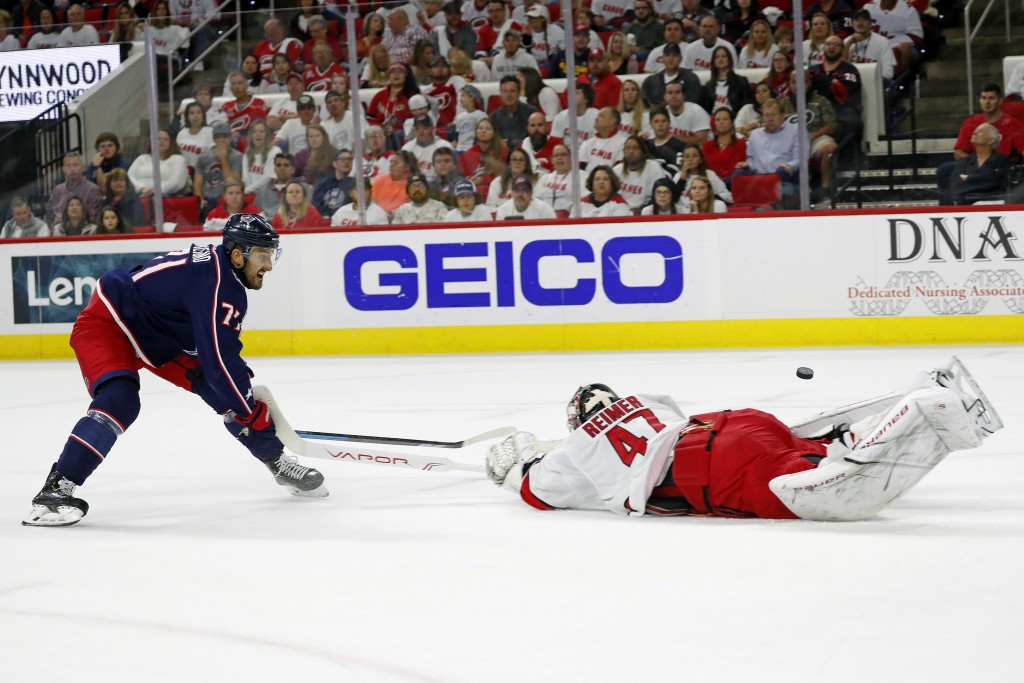 Carolina Hurricanes goaltender James Reimer (47) pokes the puck away from Columbus Blue Jackets' Nick Foligno (71) during the first period of an NHL h...