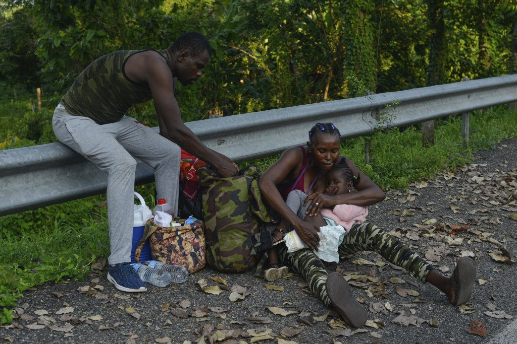 A migrant checks the diaper of a young child alongside the Highway 200 en route to Huixtla near Tapachula, Chiapas state, Mexico, Saturday, Oct. 12, 2...
