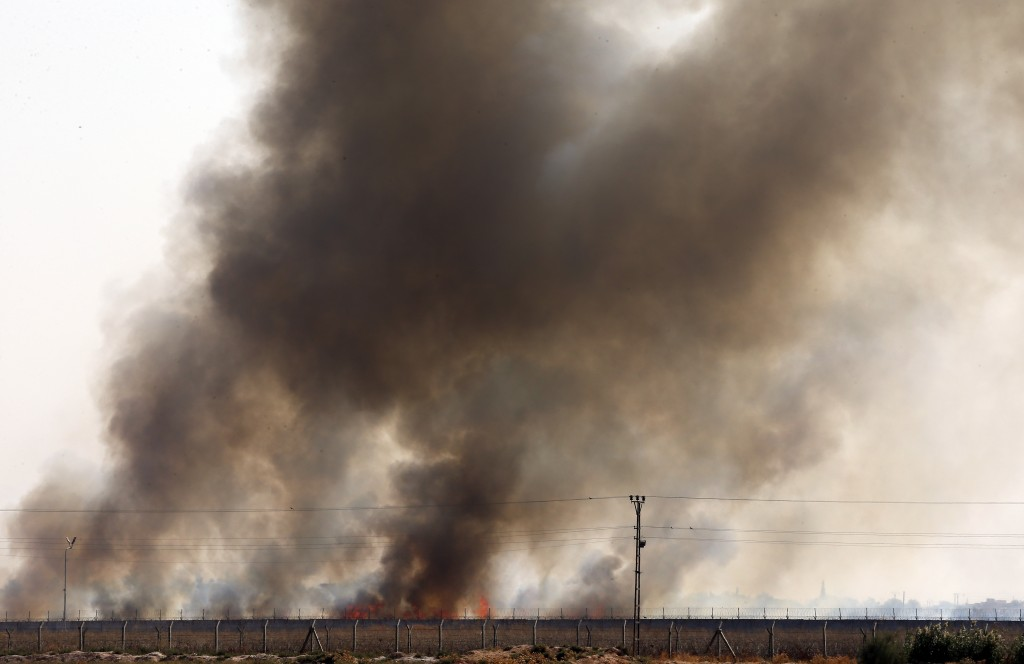In this photo taken from the Turkish side of the border between Turkey and Syria, in Akcakale, Sanliurfa province, southeastern Turkey, smoke billows ...
