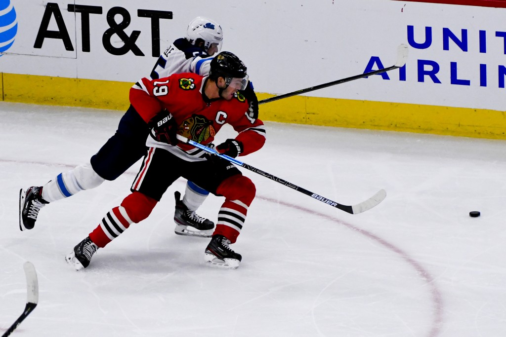 Chicago Blackhawks center Jonathan Toews (19) and Winnipeg Jets center Mark Scheifele, back, fight for the puck during the third period of an NHL hock...