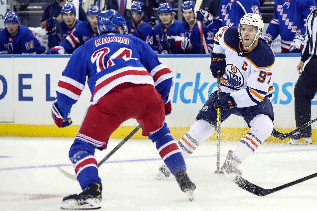 Edmonton Oilers center Connor McDavid (97) skates against New York Rangers right wing Kaapo Kakko (24) during the first period of an NHL hockey game, ...