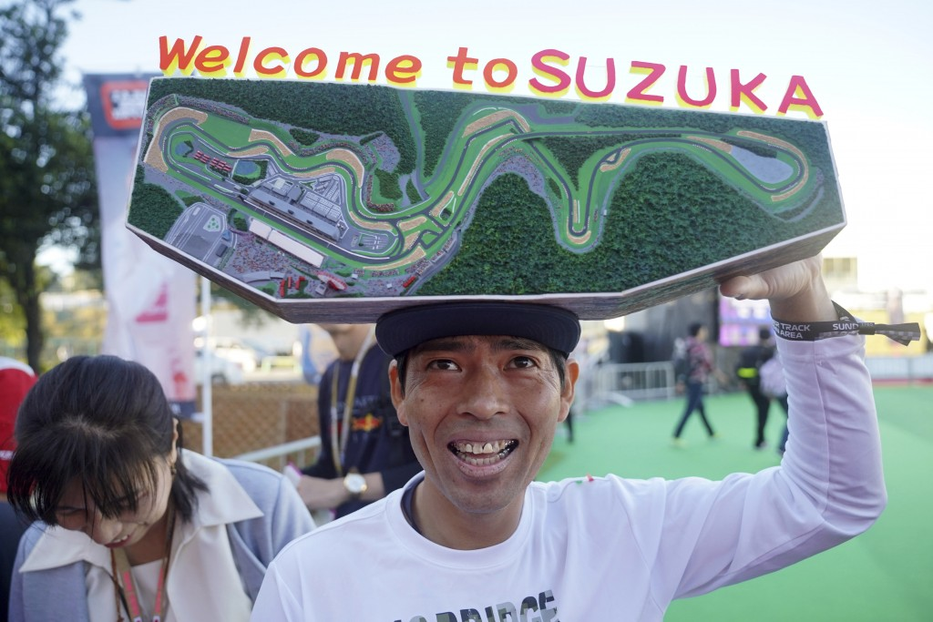 A fan with a decoration of Suzuka Circuit waits for drivers in front of the gate of the paddock ahead of the Japanese Formula One Grand Prix in Suzuka...
